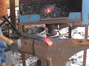 "Flat bar stock at orange heat on the end - the technique we used on Mason's cookbook holder. You heat up the section you want and hammer it quickly while it is soft, before it starts to cool and harden back up. ""Strike while the iron is hot!"" comes from this saying."